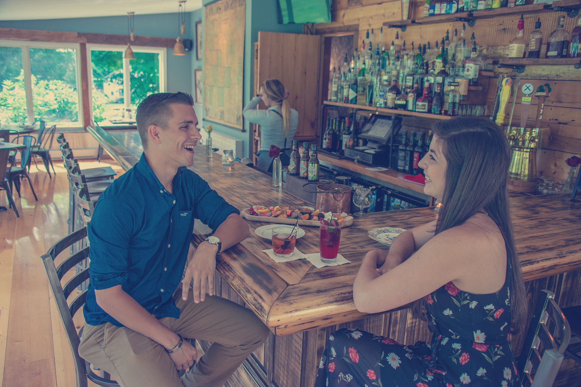 woman and man having drinks and appetizers while laughing at a bar